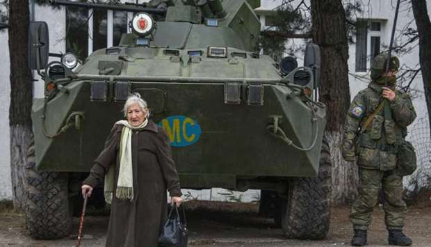 Margarita Khanaghyan, 81 walks past an APC of the Russian peacekeeping force in the town of Lachin o