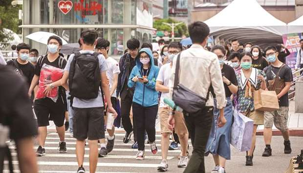 Pedestrians wearing protective masks cross a road in Taipei, Taiwan. An informal US-led alliance to
