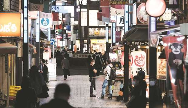 Pedestrians walk past restaurants at night in the Shinjuku district of Tokyo. As coronavirus infecti