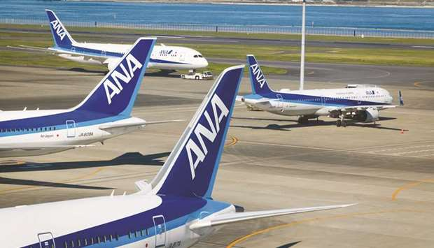A tug pulls an All Nippon Airways Co aircraft past other planes operated by the airline at Haneda Ai