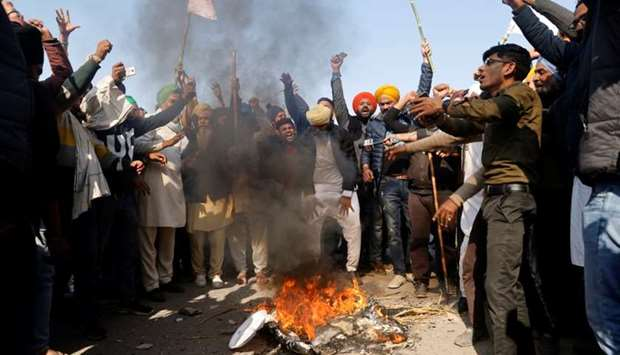 Farmers shout slogans as they burn an effigy during a protest against the newly passed farm bills at