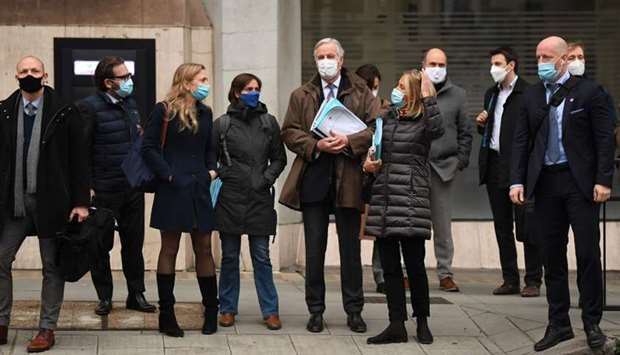 EU chief negotiator Michel Barnier (C) wearing a protective face covering, waits to cross the road a