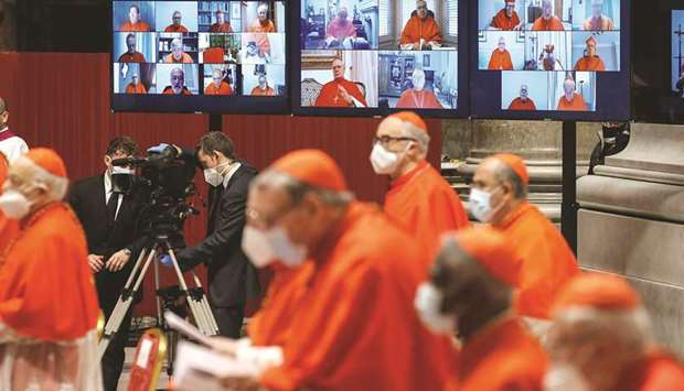 Absent cardinals appear on screens via video connection during a consistory ceremony at St Peter's B