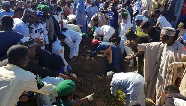 Men gather during the mass burial of people who were killed by militant attack, in Zabarmari, in the