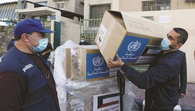 A worker unloads boxes containing ventilators delivered by the World Health Organisation (WHO) and d