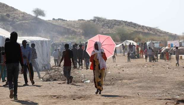 Ethiopian refugee walks with an umbrella at the Um Rakuba refugee camp which houses refugees fleeing