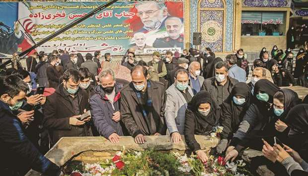 Iranian mourners attend the burial ceremony of slain nuclear scientist Mohsen Fakhrizadeh at Imamzad
