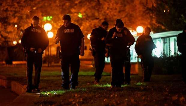 Police officers search next to a street after exchanges of gunfire in Vienna, Austria