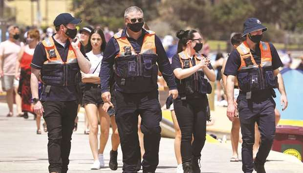 Officers patrol while people enjoy the warm weather on Melbourne's St Kilda Beach yesterday.
