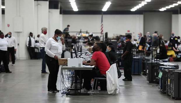 Poll workers tabulate absentee ballots at the TCF Center during Election Day in Detroit, Michigan