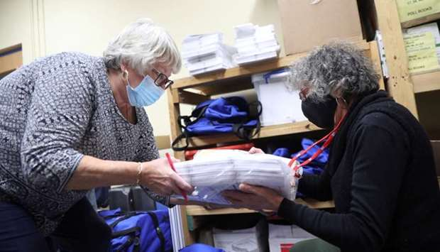 Election officials Sharon Krewson and Donna Nicolazzi unpack blue bags containing ballots after Elec