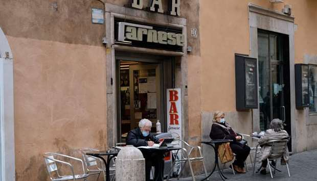 People wearing protective masks, sitting at the coffee tables of a bar near Piazza Farnese during th