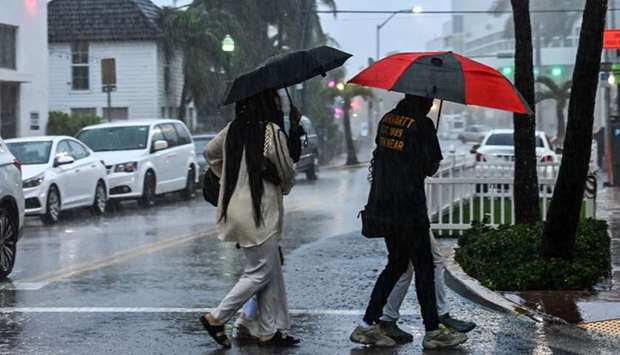 People cross the street during a heavy rain and wind as tropical storm Eta approaches south of Flori