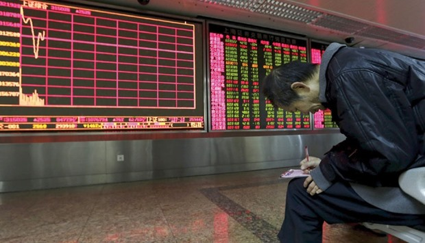 An investor takes notes of stock information in front of an electronic board at a brokerage house in