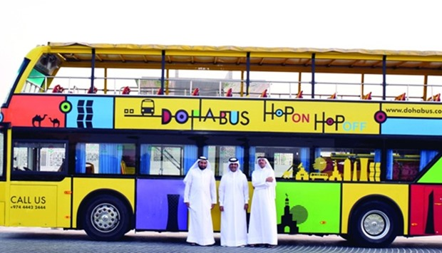 Amlak and Doha Bus officials in front of a sightseeing tour bus