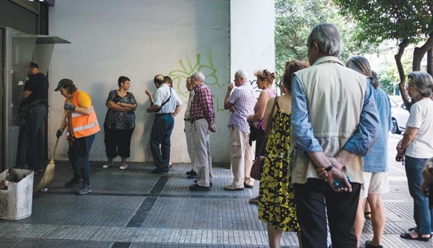 Customers form a queue outside an automated teller machine (ATM) operated by a National Bank of Gree