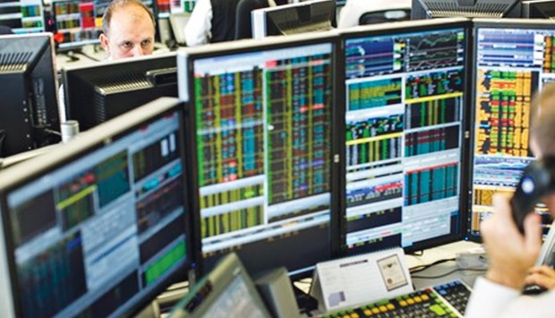 Traders monitor share prices at the London Stock Exchange. The bourse yesterday gained 0.5%.