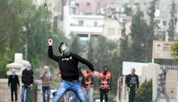 A Palestinian protester uses a sling to hurl stones towards Israeli troops during clashes