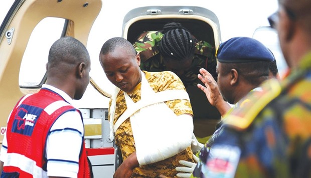 An injured Kenya Defence Force soldier steps out of a plane for a transfer to a hospital in Nairobi.