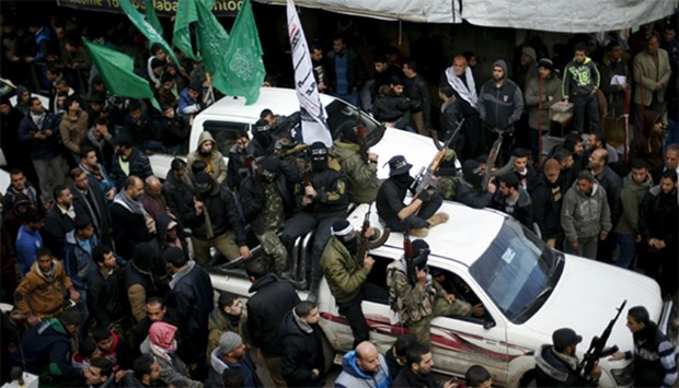 Palestinian Hamas gunmen attend the funeral of their seven comrades who were killed when a tunnel co