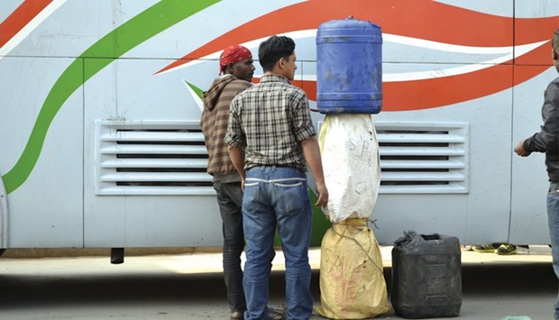 Men in Kathmandu unload fuel smuggled over the border from India on a bus.