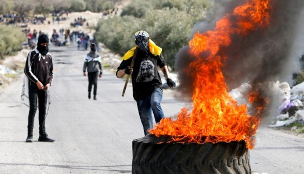 Palestinian protesters take part in a protest following the funeral of Palestinian youth Qusai Al-Am