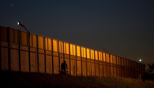 A border patrol agent drives along the US- Mexico border crossing in San Ysidro, California