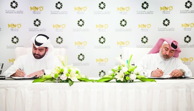 From right: Abdulla Hassan al-Mehshadi and Jaber al-Ansari signing the agreement.