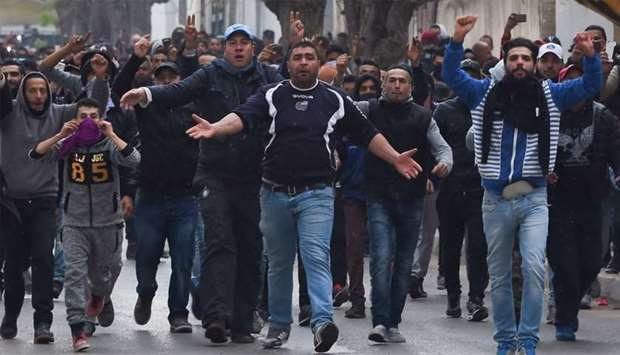 Tunisian protesters gesture towards security forces during clashes in the town of Tebourba