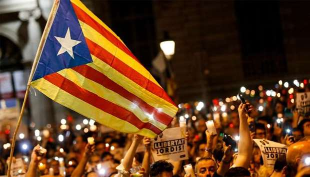 people holding candles and a Catalan pro-independence 'Estelada' flag