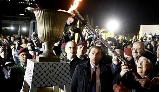 Palestinian President Mahmoud Abbas lights a torch during a rally