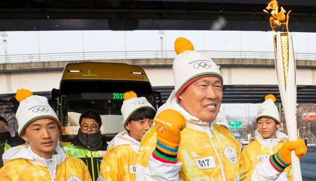 South Korean football legend Cha Bum-Kun (C) carries the Olympic flame during the PyeongChang 2018 T