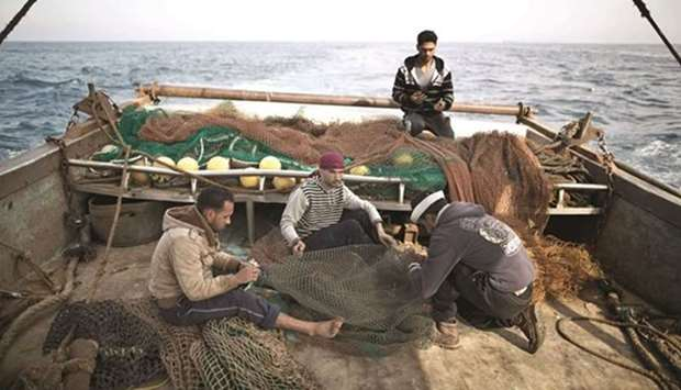 Gaza fishermen fix the nets on a boat. April 3, 2016 file picture