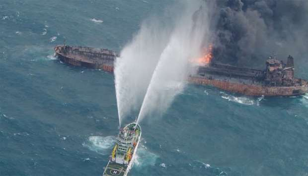 A rescue ship works to extinguish the fire on the stricken Iranian oil tanker Sanchi in the East Chi