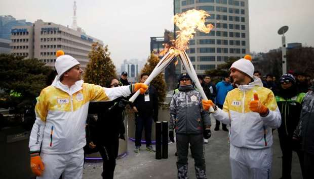 Torchbearers carry Olympic torches in Seoul, South Korea
