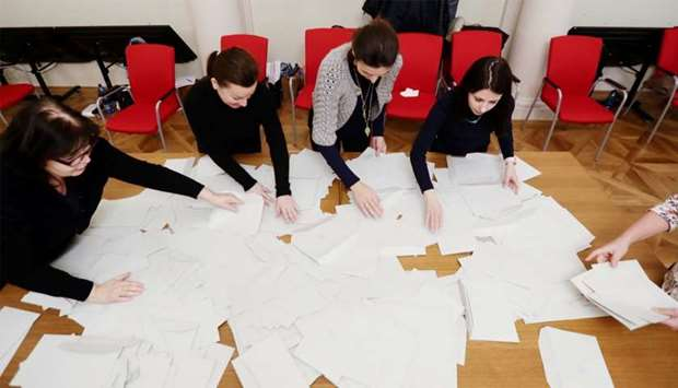 Election committee members are seen as they count votes after polling stations closed for the countr