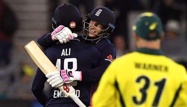 England batsman Joe Root (C) embraces teammate Moeen Ali (L) as Australia's David Warner (R) looks o