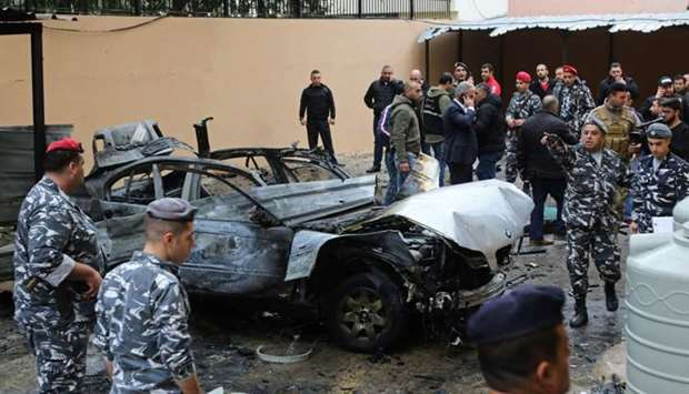 Lebanese security forces stand near a damaged vehicle following a car bomb blast in the southern Leb