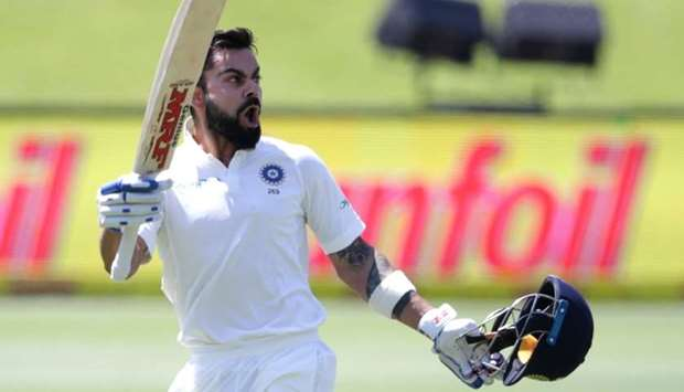 India's captain Virat Kohli raises his bat and helmet as he celebrates scoring a century (100 runs)