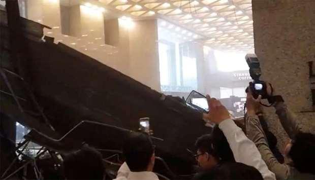 People photograph the damage seen inside the Indonesia Stock Exchange (IDX) building in Jakarta