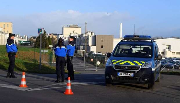 French gendarmes stand guard close to the entrance of the Celia dairy company's infant milk factory