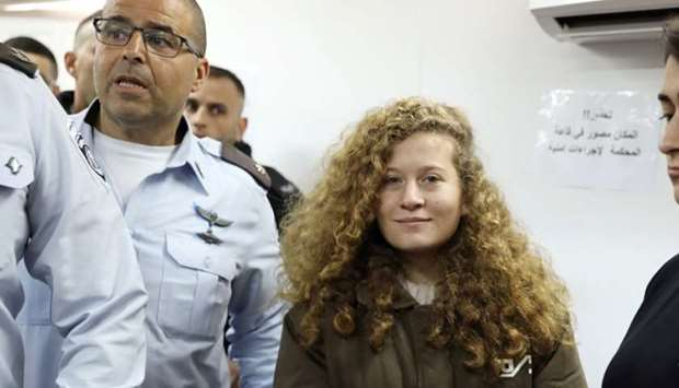 Palestinian teen Ahed Tamimi enters a military courtroom escorted by Israeli security personnel at O