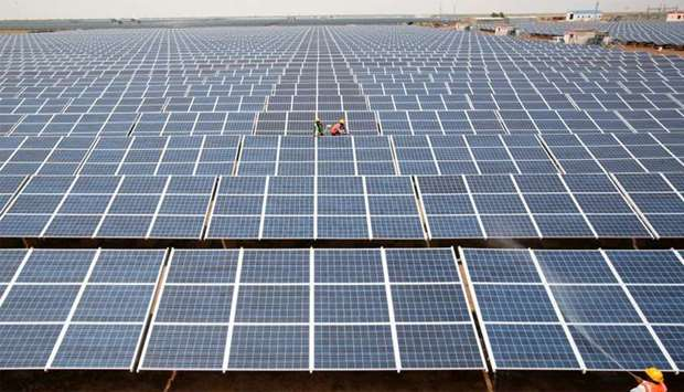 Workers install photovoltaic solar panels at the Gujarat solar park under construction in Charanka v