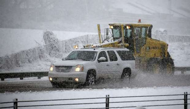A vehicle passes a snow plow as it moves along Wade Avenue during a snow storm
