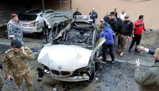 People inspect the car damaged in a bomb attack at Sidon in southern Lebanon on January 14, 2018