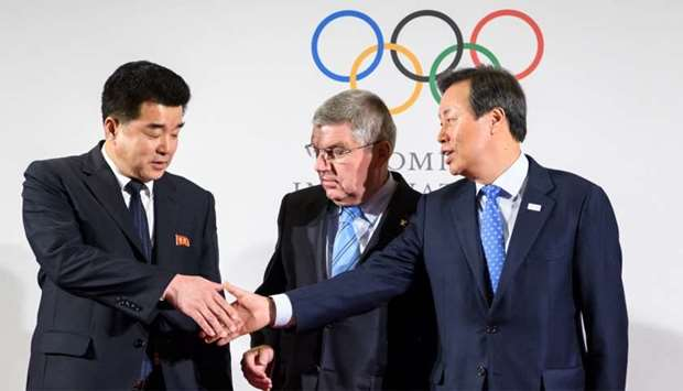 International Olympic Committee (IOC) President Thomas Bach (C) poses with North Korea's Sports Mini