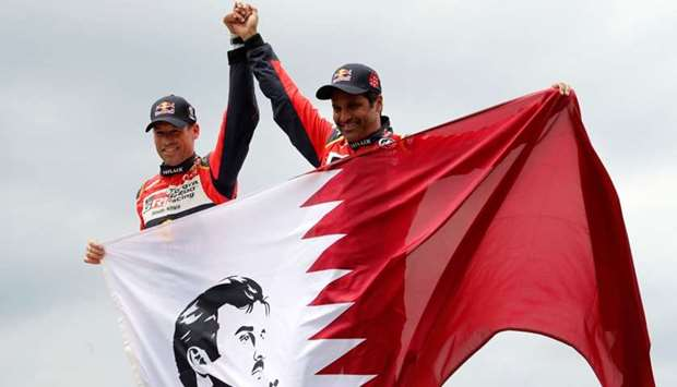 Nasser Al-Attiyah of Qatar and co-pilot Matthieu Baumel (L) of France celebrate after obtaining the