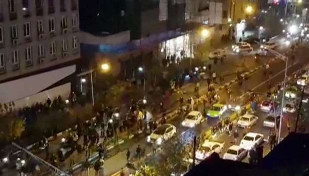 Image grab shows a group of men protesting in a street in Tehran