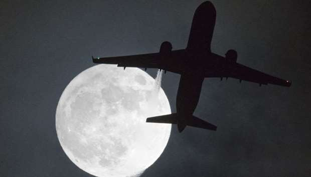 "A plane flys in front of a ""super moon"" on its approach to London Heathrow Airport"