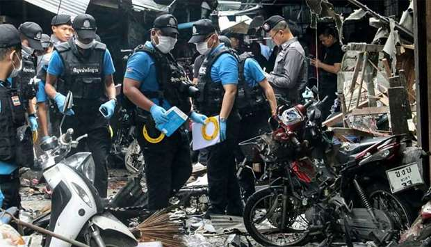 A Thai forensics unit scours the aftermath of a motorcycle bombing which killed three civilians and